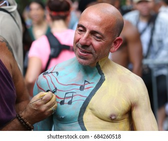 NEW YORK - JULY 22, 2017: Artists paint 100 fully nude models of all shapes and sizes during 4th NYC Body Painting Day featuring artist Andy Golub on Washington Square in New York