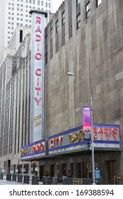 NEW YORK - JULY 4: People walk past Radio City Music Hall at 6th Avenue on July 4, 2013 in New York. Radio City exists since 1932 and is registered in U.S. National Register of Historic Places.