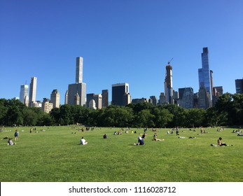 NEW YORK - JUNE 12, 2018: People in Sheep Meadown Central park on sunny day in Manhattan with buildings in background.