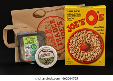 New York, June 13, 2017: Small sampling of food items purchased from Trader Joe's grocery store along with a branded brown paper bag stand against black background.