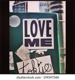 "NEW YORK - JUNE 2014: ""Love Me"" sticker on a metal street post on June 15, 2014 in Manhattan, New York."