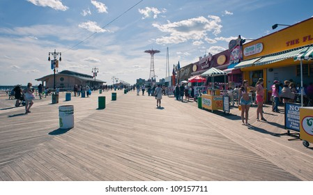 NEW YORK - JUNE 27: Riegelmann Boardwalk with Parachute Jump in the background on June 27, 2012 in Coney Island, NY. The Parachute Jump is 262 feet (80 m) tall and weighing 170 tons (150 tonnes).