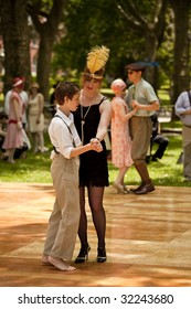 NEW YORK - JUNE 6: Mother and son in period clothing dance at 5th Annual Jazz age concert and picnic on Governors Island on June 6 2009 in New York