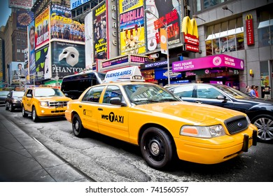 New York, Manhattan, NY - 9 JUNE, 2016: A busy intersection on Times Square. Yellow cabs in front of the scene with famous billboards in the back.