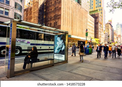 New York Manhattan, USA 18 May 2019. Woman waiting at the bus station with advertising board of Chanel brand and it's time to go home after work of city life downtown in New York