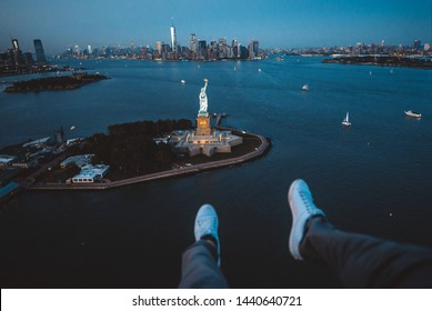 New york and Manhattan view from the helicopter . Man watching the city from the sky. Making a tour on a doors off helicopter to central park,financial district and statue of liberty
