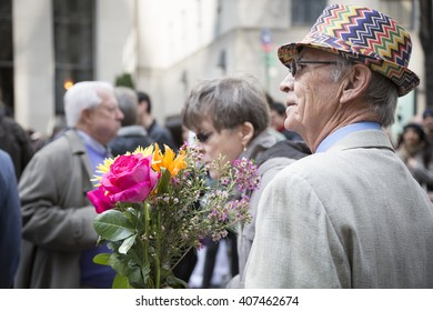 NEW YORK - MAR 27 2016: A man wearing a colorful straw hat holds a bouquet of flowers on Easter Sunday during the traditional Easter Bonnet Parade along 5th Ave in Manhattan on March 27, 2016.