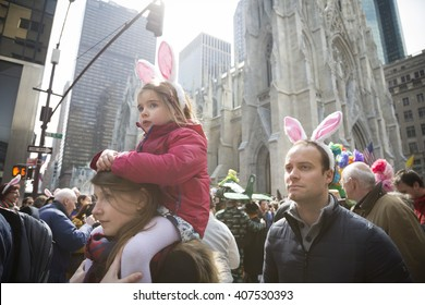NEW YORK - MAR 27 2016: A young girl wearing Easter Bunny ears sits on a womans shoulders above the crowd on 5th Ave Easter Sunday at the traditional Easter Bonnet Parade in Manhattan, March 27, 2016.
