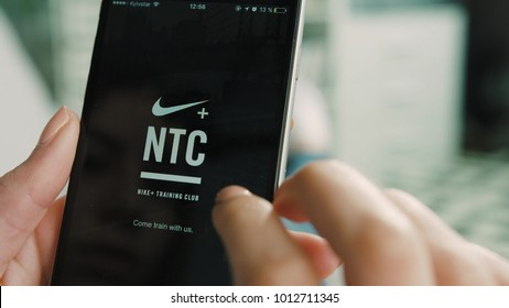 New York - March 10, 2017: Woman hands get ready to the running, turn on nike run app on smart phone while lying on the coach in the living room at home. Close up.