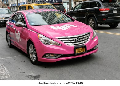 New York, March 11, 2017: A pink car with Lyft logo is driving along 14th street in Manhattan. Lyft offers a convenient way to hire a ride using a smart phone.