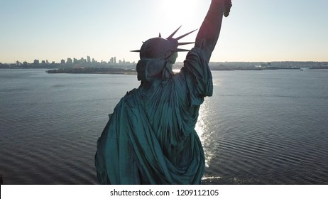 NEW YORK - MARCH 11, 2018: rear view of Statue of Liberty from rear over water in NYC. The famous statue is a colossal neoclassical sculpture on Liberty Island in NY Harbor.