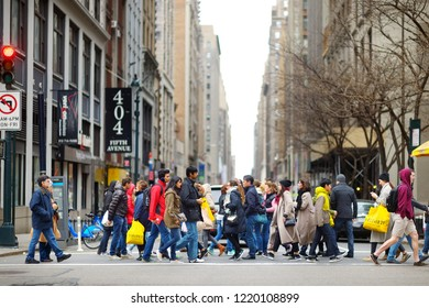NEW YORK - MARCH 16, 2015: People crossing a street in downtown Manhattan. Tourists and newyorkers walking across a busy NYC crosswalk.