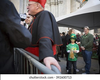 NEW YORK - MARCH 17, 2016: A young boy wearing fun St Patricks Day attire stands next to Timothy Cardinal Dolan Archbishop of New York by Saint Patricks Cathedral on St Patricks Day in Manhattan.
