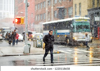 NEW YORK - MARCH 19, 2015: Cars, taxi cabs and people rushing on busy streets of downtown Manhattan during massive snowfall. Snowy winter weather in NYC, USA.
