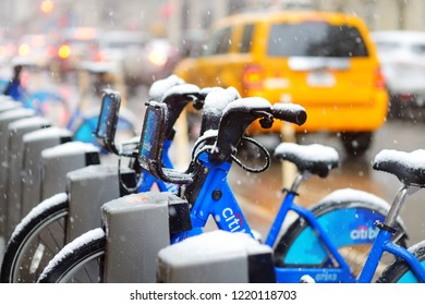 NEW YORK - MARCH 19, 2015: Row of Citi bike rental bicycles at docking station in New York City during massive snowfall. Shared bikes lined up in the street of New York, USA.