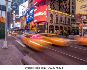 New York, New York - March 29, 2018: Famous New York City yellow cabs streaking through Times Square early in the morning.