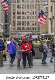 New York, New York - March 30, 2018: Tourist looking to buy tickets for the Big Bus tour outside the Rockefeller Center.