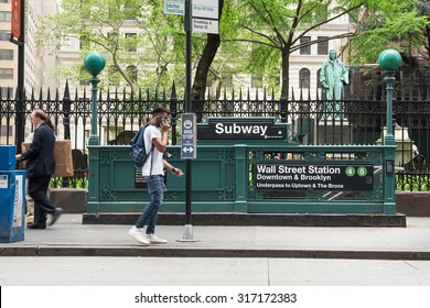 NEW YORK - MAY 12, 2015: People walking on the street in front of Wall St. Subway. The NYC Subway is one of the oldest and most extensive public transportation systems in the world with 468 stations.