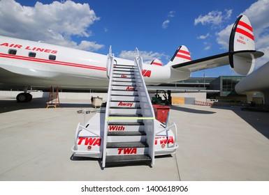 NEW YORK- MAY 16, 2019: TWA Hotel's 1958 Lockheed Constellation airplane in front of the landmark TWA Flight Center building designed by Eero Saarinen at the JFK Airport in New York