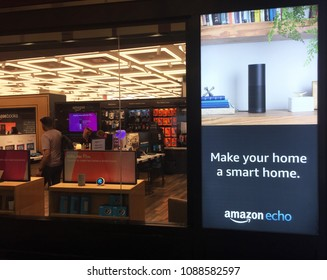 NEW YORK- MAY 2018: Black Amazon Echo , Alexa Voice Service activated recognition system advertised outside Amazon book store. E-commerce biz sells Kindles, Fire TV tablet Alexa Echo AMZN smart home