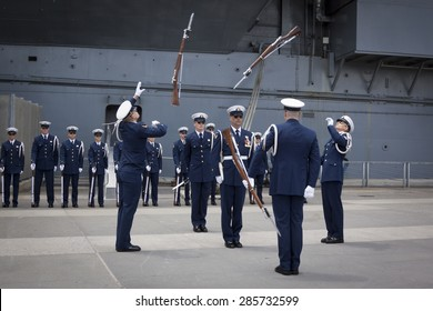 NEW YORK - MAY 22 2015: The US Coast Guard Ceremonial Honor Guard Silent Drill Team  perform an air-toss movements of rifles with fixed bayonets on Pier 92 next to the Intrepid during Fleet Week NY.