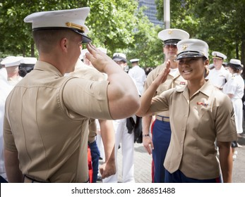 NEW YORK - MAY 22 2015: A US Marine Corpsman receives a salute from a fellow Marine after the promotion ceremony at the National September 11 Memorial site during Fleet Week 2015.