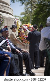 NEW YORK - MAY 25 2015: A US veteran helps lay a wreath of flowers at the annual Memorial Day Observance service held at the Soldiers and Sailors Monument in Manhattan during Fleet Week NY 2015.