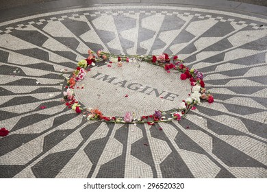 NEW YORK - May 25, 2015: People gather at Strawberry Fields in Central Park, New York City. Strawberry Fields is a memorial to honour the memory of John Lennon.