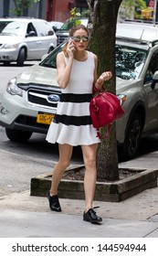 New York, May 29, 2013. Olivia Palermo wears a white dress and carries red bag as she runs errands in NYC.