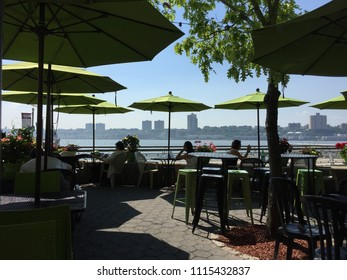NEW YORK - MAY 29, 2018: People relax, eat, drink in Riverside Park in Manhattan Upper West Side on summer day on the Hudson River.