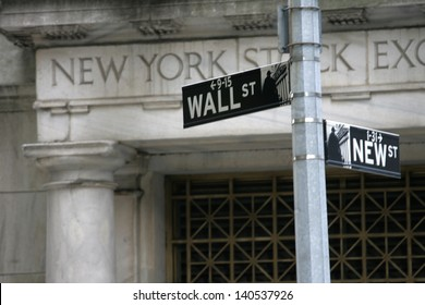 NEW YORK - MAY 30: A Wall Street street sign is shown on May 30, 2013 in New York City. The Exchange building was built in 1903.