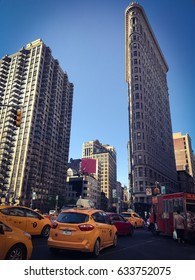 NEW YORK, NEW YORK - May 4th 2017: Flat iron building in New York with taxis in the street
