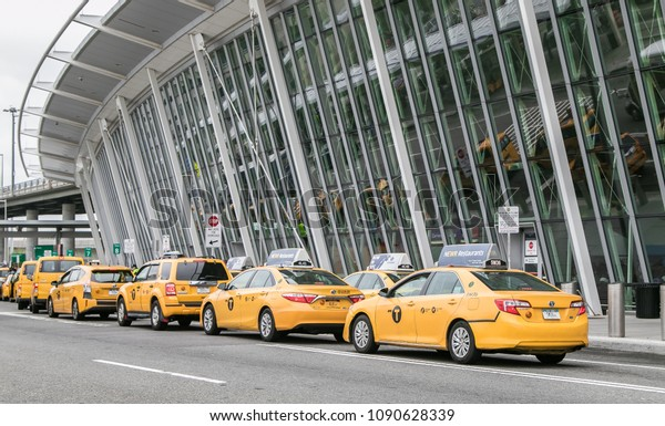 New York, May 5, 2018: Yellow taxi cabs have formed a line in front of JFK airport's terminal 4.