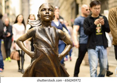 NEW YORK - MAY 6: Tourists walk past a bronze sculpture called the Fearless Girl on May 6, 2017 in New York City's Financial District. It was installed one day before International Women's Day 2017.