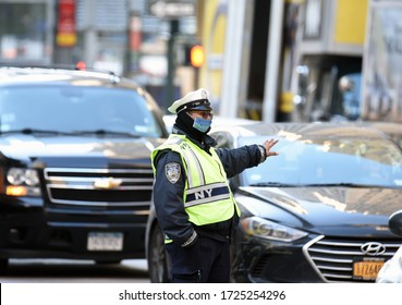 NEW YORK - MAY 8, 2020: A police officer directs traffic in the center of New York City and wears a colored Coronavirus protection mask. Police controls on the road. Covid-19 global warning.