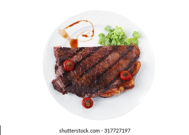 new york meat style beef steak fillet on white plate with hot chili pepper and green salad isolated over white background with stainless steel cutlery
