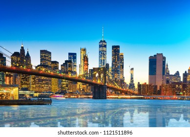 New York night view of the Lower Manhattan and the Brooklyn Bridge across the East River. USA.