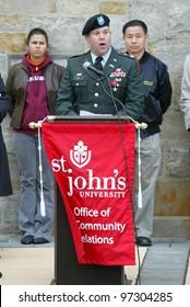 NEW YORK - NOV 11: Bronze Star recipient Andy Lyons speaks as NYC Councilman John Liu (R) listens at a Veteran's Day Memorial service at St. John's University November 11, 2005 in Queens, NY.