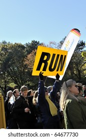 "NEW YORK - NOV. 7: An unidentified woman with yellow scarf and yellow sign saying ""Run"" cheers runners near Mile 24 in the 2010 New York City Marathon in Central Park on Nov. 7, 2010 in New York, NY."