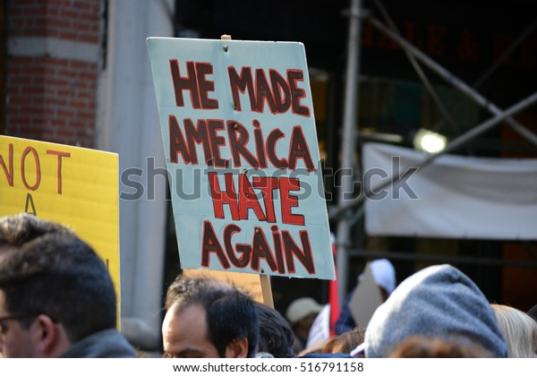 """New York, New York. - November 12, 2016: People carrying signs at a """"Trump is not my President"""" rally against President elect Donald Trump in Manhattan in 2016 in New York City."""