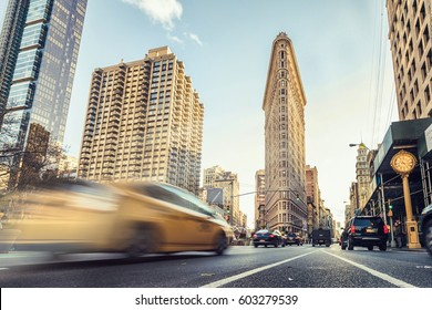 NEW YORK - November 18: Blurred View of Taxi Cabs at Busy Street Intersection and Historic Flatiron Building on Fifth Avenue at Sunset on November 18, 2015 in Manhattan, New York, USA