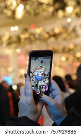NEW YORK, NEW YORK- NOVEMBER 2017: A woman takes a video with her cell phone of holiday decorations inside of Macy's retail store in New York City.