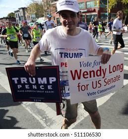 NEW YORK - NOVEMBER 6, 2016: Trump supporter with political signs runs at New York City Marathon. It traverse 26.2 miles through all five NYC boroughs to the finish line in Central Park, Manhattan