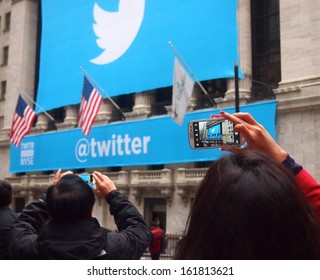 NEW YORK, NOVEMBER 7: A woman photographs the Twitter logo outside the New York Stock Exchange in New York City, November 7, 2013. Twitter was debuting as a publicly traded company.
