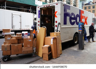 NEW YORK, NY -1 FEB 2020- View of a pile of packages by a FedEx delivery truck parked on the street in Manhattan, New York City, United States.