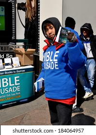 New York, NY - 27 March 2014:  Young Asian man distributing religious flyers during a Bible Crusade on West 34th Street and Broadway