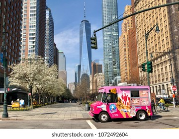 NEW YORK, NY - APRIL 14, 2018: A pink ice cream truck drives past the skyscrapers in downtown Manhattan with Freedom Tower visible in the background.