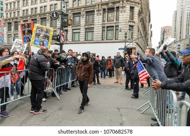 New York, NY - April 15, 2018: Pro and contra President Trump agenda argue across police line during anti-US rally by Take Action NYC Leftists organizations on Herald Square