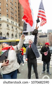 New York, NY - April 15, 2018: Woman trying to block American flag with Palestinian flag during anti-US rally by Take Action NYC Leftists organizations on Herald Square