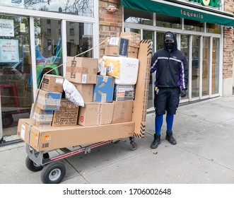 New York, NY - April 16, 2020: FedEx worker Kelvin Nunez as essential worker seen delivering packages amid COVID-19 pandemic in Inwood neighborhood of Manhattan